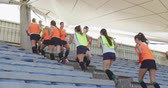 amontoado : Side view of a teenage Caucasian female hockey team running up and down steps between stadium seats at a sports field, warming up before playing on the hockey pitch, slow motion