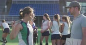 Side view of a Caucasian male coach standing and explaining a game plan to a teenage Caucasian female hockey player on the pitch at a sports stadium, the rest of the team standing in the background, slow motion