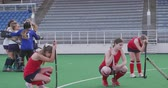 amontoado : Side view of a team of teenage Caucasian female hockey players holding their hockey sticks and kneeling on the pitch after losing the match, in the background the winning team in a huddle celebrating their victory, slow motion