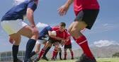 campo da rugby : Side view of a group of Caucasian male rugby players from two teams wearing team strips, playing on a pitch, one team tackling teh other for possession of the ball, in slow motion