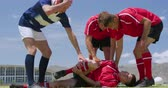 preocupacion : Low angle front view of a group of Caucasian male rugby players from opposing teams wearing team uniforms, gathered around an injured player lying the ground clutching his leg on a rugby pitch during a match, in slow motion