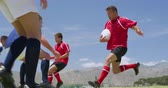 Side view of a group of Caucasian male rugby players from two opposing teams, wearing team strips, playing on a pitch, making a pass and being tackled, in slow motion Wideo