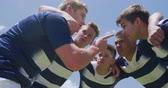 amontoado : Low angle side view of a multi-ethnic group of male rugby players training on a pitch in a motivational huddle, with arms around shoulders discussing a game plan, in slow motion