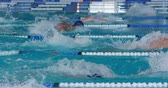 Side view of multi-ethnic group of male swimmers at swimming pool, racing each other in lanes, swimming butterfly in slow motion