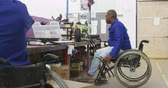 colegas de trabalho : Side view of two African American male workers in a workshop at a factory making wheelchairs, at a workbench assembling parts of a product, one of the workers is disabled and uses a wheelchair to move around the factory