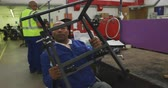 Front view of an African American male worker in a workshop at a factory making wheelchairs, sitting at a workbench assembling the frame of a product and checking it, he is sitting in a wheelchair, other workers are talking and working in the background