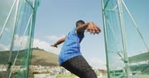 柔軟 : Low angle front view of a mixed race male athlete practicing at a sports stadium, throwing discus, slow motion. Track and Field Sports Training in Stadium.