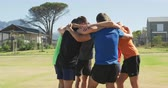 colete : Side view of a multi-ethnic group of male runners training at a sports field, standing in a motivational huddle with arms around each other. Track and Field Sports Training in Stadium, in slow motion