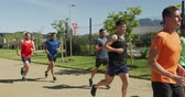Side view of a multi-ethnic group of male runners training at a sports field, running together on a path. Track and Field Sports Training in Stadium, in slow motion