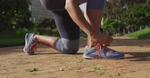 sval : Side view low section of a young Caucasian woman wearing sports clothes tying her shoe laces during a workout in a park