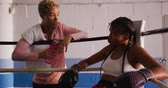 törülköző : Front view of a mixed race female boxing coach with short curly hair giving a holding a bottle of water and leaning on the ropes talking to a mixed race female boxer with long, dark plaited hair sitting in the corner of a boxing ring taking a rest during