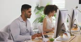 race : Side view of a mixed race woman and man working in a creative office, sitting at desk looking at computer screens, discussing Stock Footage