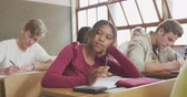 nadenken : Front view of a teenage African American girl in a school classroom sitting a desk, concentrating and thinking, with teenage male and female classmates sitting at desks around her working Stockvideo