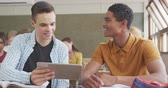 nadenken : Front view close up of a teenage Caucasian boy and teenage mixed race boy in a school classroom sitting a desk, using tablet together and talking, and writing in their books, with teenage male and female classmates sitting at desks working in the backgoun