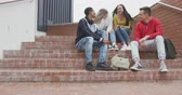 女子生徒 : Front view of a multi-ethnic group of teenage male and female school pupils with schoolbags hanging out and talking, sitting on steps in their school grounds, in slow motion