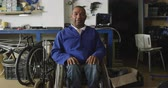 один человек : Portrait of an African American male worker in a workshop at a factory making wheelchairs, turning and looking to camera and smiling, sitting in a wheelchair