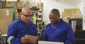 collega : Front view of a mixed race male supervisor and an African American male worker in a storage warehouse at a factory making wheelchairs, standing and talking at a workbench, the supervisor using a tablet and his colleague using a laptop computer Stockvideo