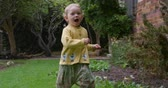 gozo : Front view of a Caucasian toddler with a yellow vest enjoying time in garden smiling and running to camera in slow motion