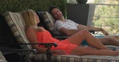 nesil : Side view of a Caucasian couple enjoying time off in summer at a hotel, on the balcony lying back on sunloungers, looking at each other and smiling. Stok Video