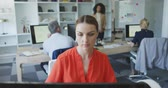 neuf : Front view of a Caucasian businesswoman working in a modern office, sitting at a desk, looking at computer screen with her colleagues working in the background in slow motion