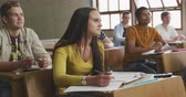 nadenken : Side view of a teenage Caucasian girl in a high school school classroom sitting a desk, concentrating and listening, with a rows of teenage male and female classmates sitting at desks around her, also listening, in slow motion