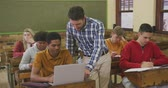 nesil : Front view of a Caucasian male teacher standing and helping a teenage mixed race boy in a high school classroom sitting a desk using laptop, with a group of teenage multi-ethnic classmates sitting at desks working in the background, in slow motion