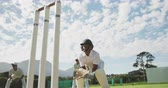 крикет : Low angle front view of a teenage African American male cricket player wearing whites, helmet and gloves, standing on the pitch playing the wicket keeper position during a cricket match, squatting, jumping and catching the cricket ball, in slow motion