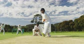nesil : Front view of a teenage Caucasian male cricket player on the pitch wearing helmet and gloves, holding a cricket bat and hitting the ball during a cricket match with other players in the background, in slow motion