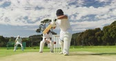 nesil : Front view of a teenage Caucasian male cricket player on the pitch wearing helmet and gloves, holding a cricket bat, failing to hit the ball and getting bowled out during a cricket match, with a wicket keeper and other players in the background in slow mo