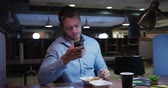 nesil : Front view of a Caucasian businessman working late in a modern office, sitting at his desk checking his smartphone, eating takeaway food taking a break