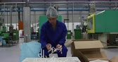 ládakeret : Front view of focused mixed race male worker working in a busy factory warehouse, wearing hair net preparing and packing plastic parts