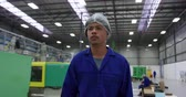 木箱 : Front view of focused mixed race male worker working in a busy factory warehouse, wearing a hair net and overalls, using a tablet computer, walking through a factory warehouse