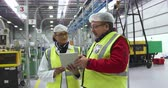 collega : Front view of a focused Caucasian male and female worker working in a busy factory warehouse, wearing hair nets and high visibility vests, using a tablet computer and discussing together