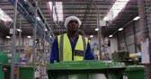 один человек : Front view of focused African American male worker working in a busy factory warehouse, wearing a hair net, overalls and a high visibility vest, walking along in a factory pusging a green bin