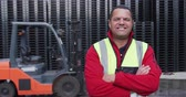 тележка : Portrait of a confident mixed race male worker working outside a factory warehouse, standing beside a forklift truck, wearing high visibility vest, smiling and looking to camera, with arms crossed, in slow motion