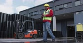 木箱 : Low angle side view of focused mixed race male worker working outside a busy factory warehouse, wearing high visibility vest and protective helmet, using a phone, with a forklift truck parked in the b