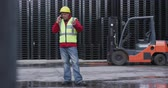 ládakeret : Front view of focused mixed race male worker working in a busy factory warehouse, wearing high visibility vest and protective helmet, talking on phone, with a forklift parked in the background, in slow motion