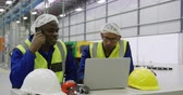 木箱 : Front view close up of a focused mixed race and African American male worker working in a busy factory warehouse, wearing hair nets, and high visibiity vests, sitting and using a laptop computer, talk