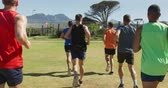yelek : Rear view of a multi-ethnic group of male runners training at a sports field, running together on a grass track. Track and Field Sports Training in Stadium, in slow motion Stok Video