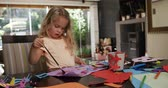 tarefa : Front view of a young Caucasian girl enjoying free time at home in the dining room, painting a picture on a violet piece of paper in slow motion.
