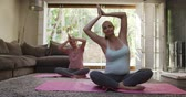 göbek : Front view of a teenage Caucasian girl and her pregnant mother enjoying free time at home in the living room, practicing yoga together in slow motion.