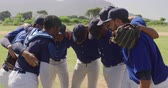 amontoado : Side view of multi-ethnic team of male baseball players, preparing before a game, in a huddle on a baseball field, focusing on a sunny day, in slow motion