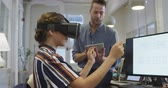 simulatie : Side view of a Caucasian businessman and mixed race businesswoman working in a modern office together, the woman wearing Virtual Reality headset the man is sitting on a desk next to her holding a digital tablet with their female colleague working in the b Stockvideo