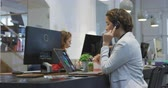 ajans : Side view of a mixed race businesswoman working in a modern office, sitting at her desk wearing phone headset talking, using a digital tablet with her colleague working in the background.