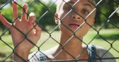 visto : Portrait close up of happy mixed race woman with short dyed blonde hair out and about in the city on a sunny day, seen through a fence, standing by a fence looking at camera in slow motion. Vídeos