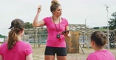 engel : Front view close up of a Caucasian female coach standing at boot camp holding a tablet computer and giving instructions to a multi-ethnic group of female friends, all wearing pink t shirts, in slow motion Stok Video