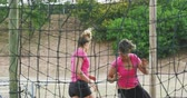 engel : Front view of a happy multi-ethnic group of women enjoying exercising at boot camp together, climbing on a net on a climbing frame and running, in slow motion