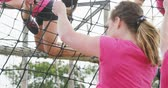 engel : Low angle rear view of multi-ethnic group of women enjoying exercising at boot camp together, climbing on nets on a climbing frame, in slow motion