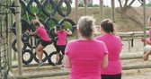 engel : Rear view of a happy multi-ethnic group of female friends enjoying exercising at boot camp together, climbing on tyres and running in slow motion