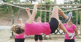 engel : Side view of a happy multi-ethnic group of female friends enjoying exercising at boot camp together, one Caucasian woman hanging upside down, moving along a rope on a climbing frame and the others watching and motivating her in slow motion